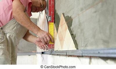 Installing Tiles - checking level - man applying ceramic...