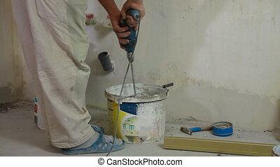 Installing Tiles - man installs ceramic tile - mixing grout
