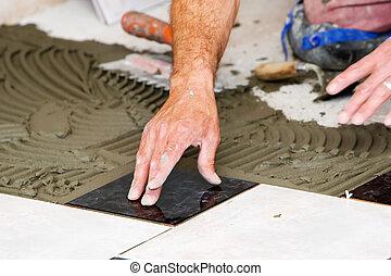 installing tiles - men installing tiles on the floor