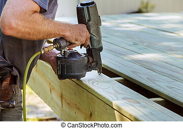 Installing Wood on deck, patio construction man using pneumatic gun
