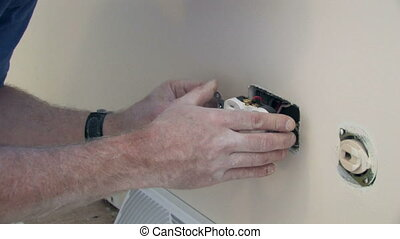 Installng Outlet - A man installs an outlet in the wall