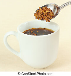 Instant coffee is poured from a spoon in cup
