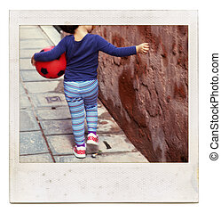 Instant film picture frame with abstract view from childhood - unrecognizable child holding red ball