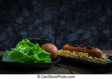Instant noodle with hotdog boiled egg and vegetable (green oak) on wooden table in dark background.