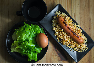 Instant noodle with hotdog, boiled egg, vegetable (green oak) and empty cup on wooden table.