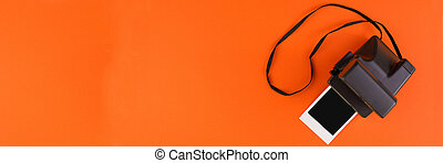 Instant photo frame and camera on a orange background. Concept of preservation of memories. Flat lay. Banner.