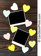 Instant photos with wooden hearts. On wooden background.