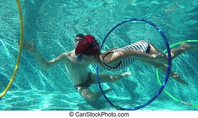 Instructor a girl swimming underwater - Instructor teaches...
