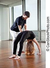 Instructor Adjusting Woman's Yoga Posture - Yoga instructor...