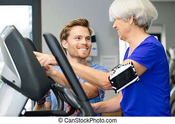 instructor aiding senior woman in gym