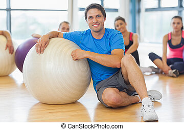 Instructor and fitness class with exercise balls at gym