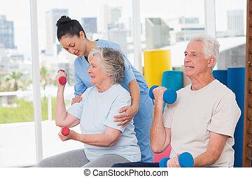 Instructor assisting senior couple