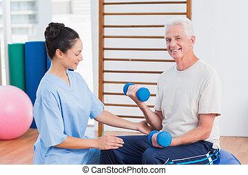 Instructor assisting senior man in lifting dumbbells