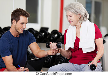 Instructor Assisting Senior Woman In Lifting Dumbbells At Gym