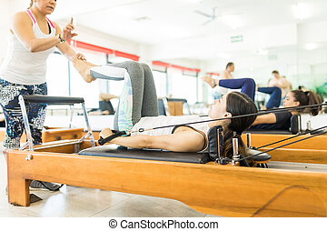 Instructor Assisting Woman On Reformer Machine In Gym