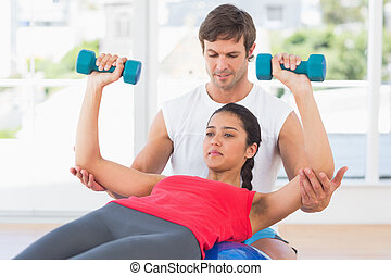 Instructor assisting woman with dumbbell weights
