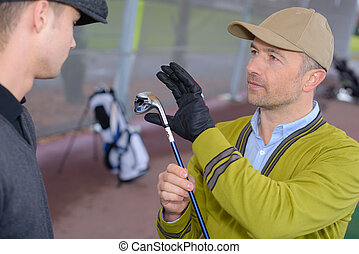 instructor assisting young man learning golf at golf course