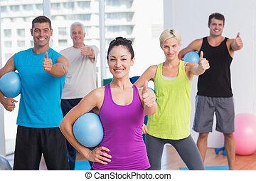 instructor, con, clase, el gesticular, pulgares arriba, en, gimnasio