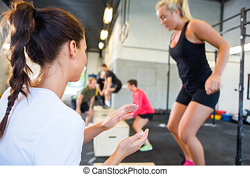Instructor Encouraging Athlete In Box Jumping - Female gym...
