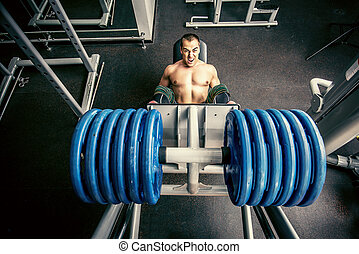 instructor - Muscular man weightlifter doing leg presses in...