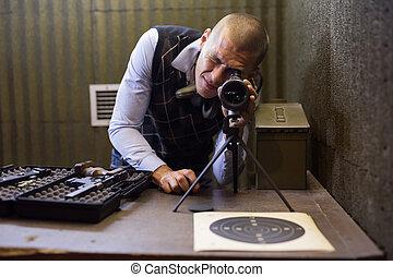 Instructor of shooting range looks through spyglass at target