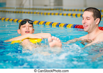 instructor teaches the boy swimming in a pool
