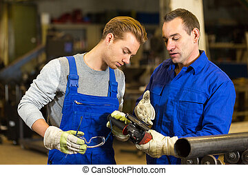 instructor teaches trainee how to use an angle grinder -...