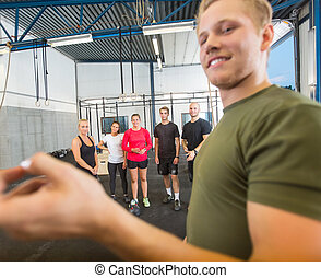 Instructor Training Athletes At Gym - Young male instructor...