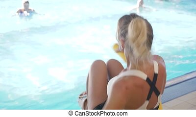Instructor training women aqua gymnastic in swimming pool....