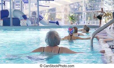 Instructor training women aqua gymnastic in swimming pool....