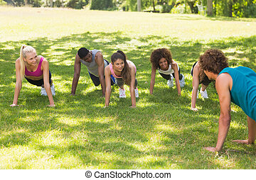 Instructor with fitness class doing push ups in park