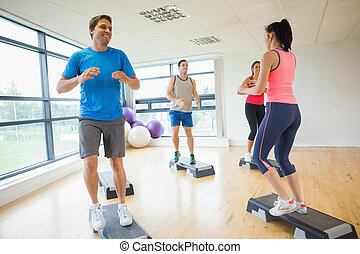 Instructor with fitness class performing step aerobics exercise