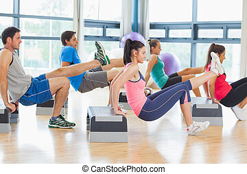 Full length side view of instructor with fitness class performing step aerobics exercise in gym