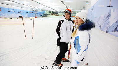instructor with girl waiting till other people go down to ski on slope and then start themselves