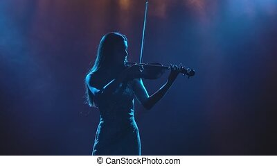 Instrumental solo performance of a classical live melody on a violin. A young girl violinist is silhouetted. Slow motion. Close up