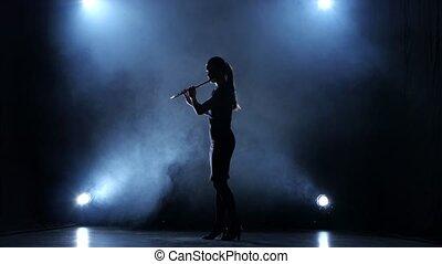 Instrumentalist female plays on wind instrument classical melody. Smoky studio