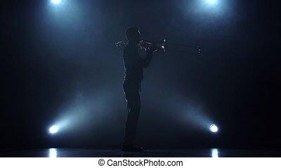 Instrumentalist plays on trumpet melody in slow motion. Smoke studio