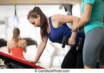 instrutor aptidão, ajudando, menina jovem, fazendo, exercícios, em, ginásio