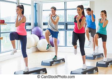 instrutor, com, classe aptidão, executar, aeróbica passo, exercício