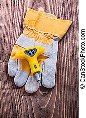 Insulated electric screwdriver and protective glove on wood ...