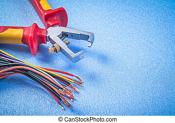 Insulated wire strippers electric cables on blue background ...