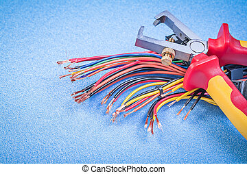 Insulated wire strippers set of electric cables on blue ...