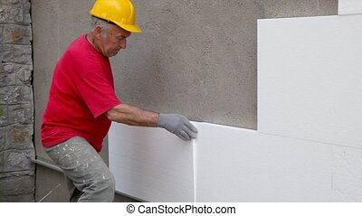 Insulation of house facade - Worker placing styrofoam,...