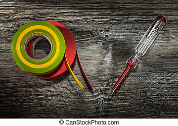 Insulation tapes insulated screwdriver on wooden board.
