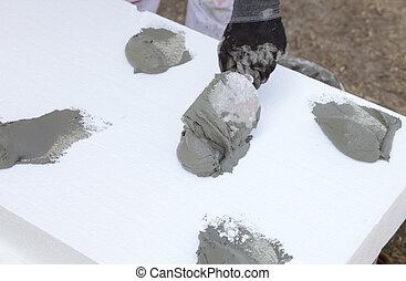 Trowel spreading mortar on styrofoam insulation of wall