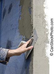 Insulation - Trowel spreading mortar on styrofoam insulation...