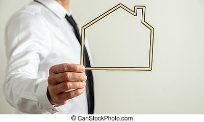 Insurance agent holding a paper cut frame of a house
