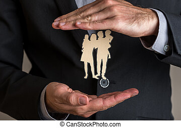 Insurance agent making protecting gesture around a paper cut silhouette of a family