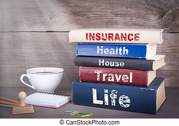insurance concept. Stack of books on wooden desk