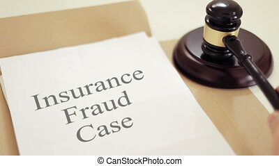 Insurance fraud written on legal documents with gavel -...